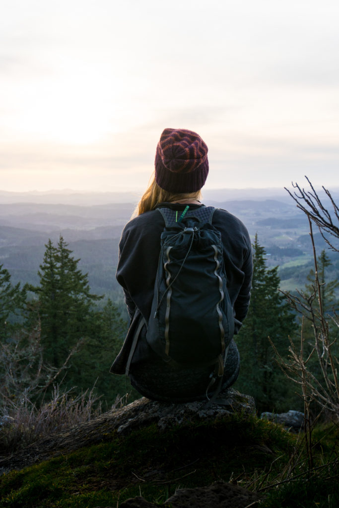 A woman hiker sits at the summit of a climb wearing a hat and backpack watching the sunset on the horizon below